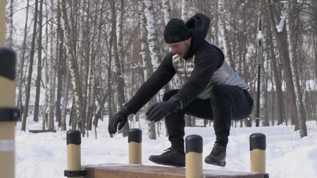 Young man jumping on bench in winter park during crossfit training outdoor Stock Photo