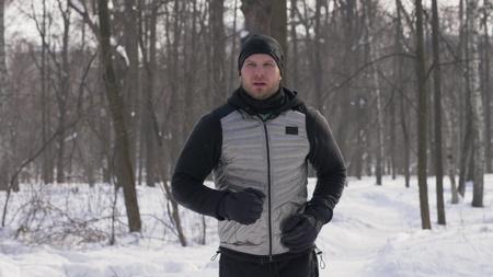 Sport man running in winter city park during morning jog. Jogging in winter forest
