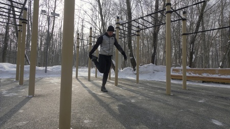 Athlete man doing fitness exercise during outdoor training at winter day