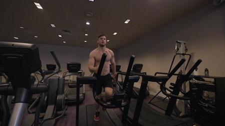 Muscular man doing cardio training on treadmill in healthy club slow motion