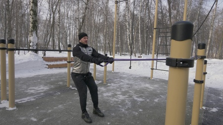 Bodybuilder training anaerobic exercise with expander on outdoor winter training Stock Photo
