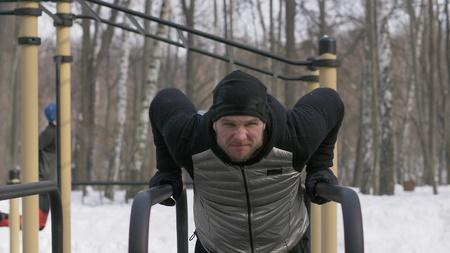 Athlete man training push ups exercise on bar on winter sport ground
