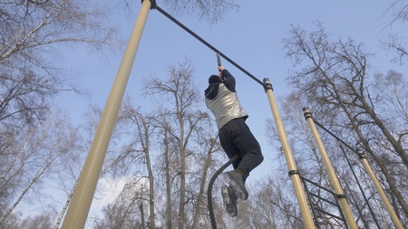 Strong man climbing on rope during outdoor workout on sport ground Stock Photo