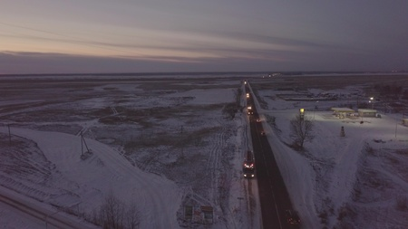 Petrol tanker with flashers standing on roadside on winter highway aerial view