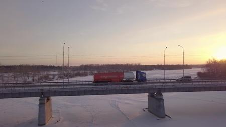 Gasoline truck moving along bridge over frozen river against winter landscape