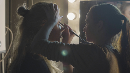 Visagiste applying eye shadow on eyelid while makeup face to woman in studio Stock Photo