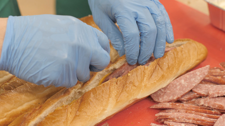 Hands chef cook putting pieces sausage in baguette in restaurant kitchen closeup Stock Photo