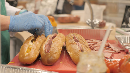 Hands cook putting pieces sausage in cut up baguette in fast food cafe Stock Photo