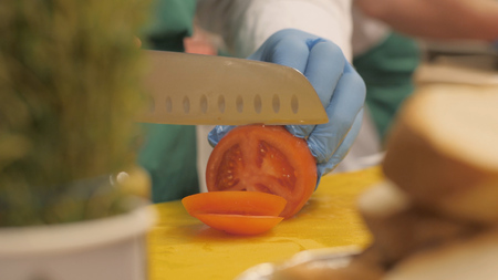 Hands of cook using knife for cutting tomato on circle slices and pieces in restaurant