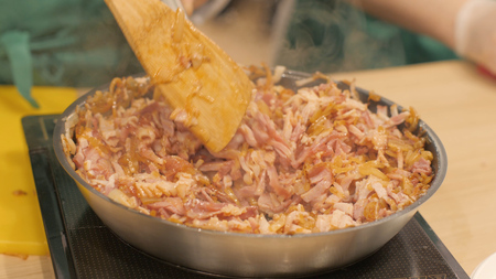 Cook mixes finely chopped pork steak and onions during stewing in frying pan Stock Photo