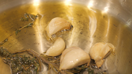 Close up garlic cloves fried in oil with spices and herbal in oil on frying pan