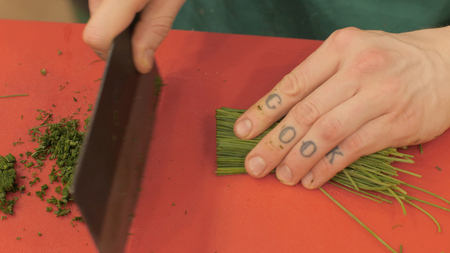Hands cook with tattoo cutting fresh greens on board in kitchen top view