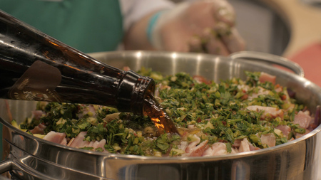 Chef cook pouring beer in pot with finely chopped pork shank while cooking
