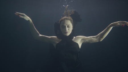 Brunette woman underwater swimming pool on dark background Stock Photo
