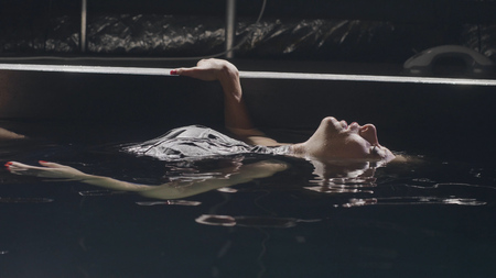 Young woman lying on smooth surface water in swimming pool on dark background