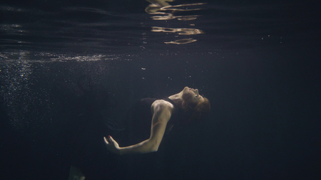Young woman in black dress swimming underwater in pool while video shooting