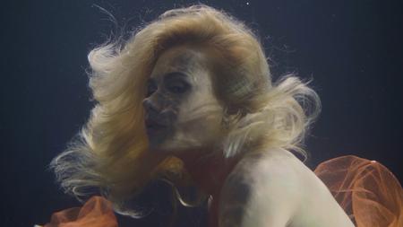 Attractive woman in orange dress underwater in swimming pool Stock Photo