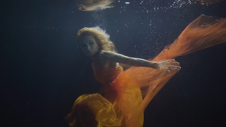 Mysterious woman swimming like mermaid under water in on dark background
