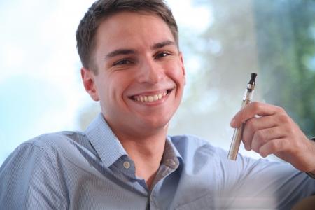 Young happy smiling man smoking electronic cigarette e-cigarette