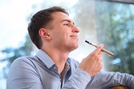 Young happy smiling man smoking eletronic cigarette e-cigarette