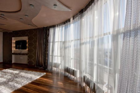 Groothoek weergave van een panoramisch raam met vitrage in moderne woonkamer