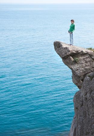 Junge schlanke Frau, die einsam am Rand der Klippe über dem Meer