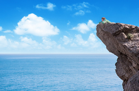 edge of cliff: Young slim lonely woman laying at the edge of mountain cliff above the sea Stock Photo