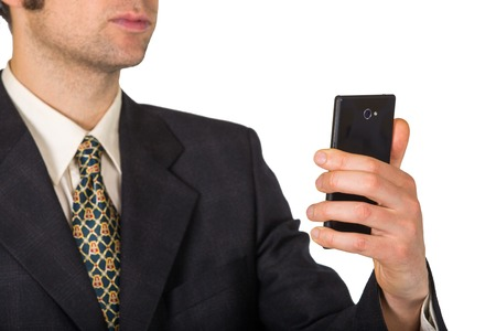 Man in suit and tie is watching at his black smartphone photo