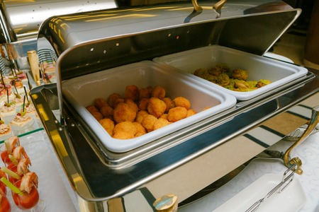 crusted: Catering - served table with nuggets and other hot snacks Stock Photo