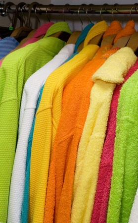 coathangers: Row of coat-hangers with bright colored bathrobes in the shop