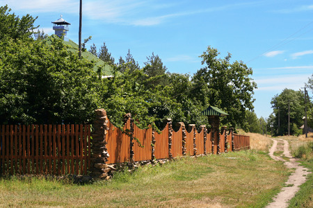 cottage fence: Small cottage behind the fence in the countryside