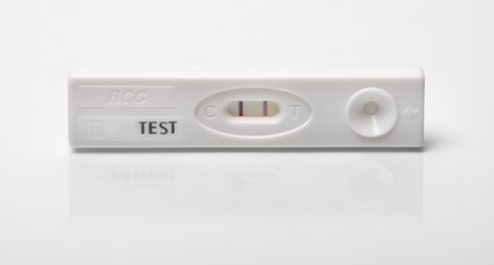 first miracle: Positive pregnancy test shoot with reflection on a white background Stock Photo