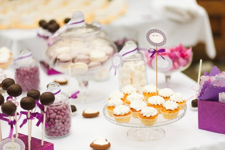 Served festive candy bar table with cupcakes and other desserts