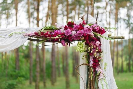 Detail der Hochzeitsdekoration - Holzbogen Ecke mit Blumen im Wald Standard-Bild