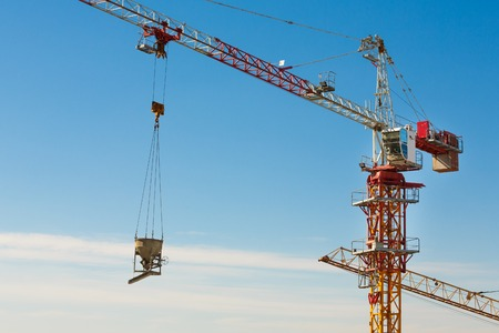jib: Tower crane lifting up a cement bucket at construction area against blue sky Stock Photo