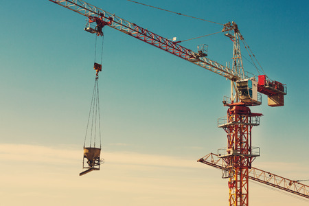 assemblage: Tower crane lifting up a cement bucket at construction area against blue sky Stock Photo