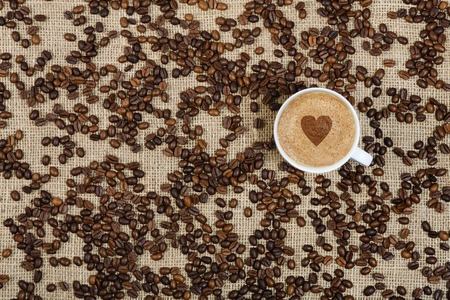 sacking: Coffee cup and beans scattered on sacking background