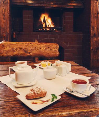 desayuno romantico: Desayuno romántico cerca de la chimenea - té, magdalenas y croissants
