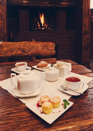 petit dejeuner romantique: Romantic breakfast near fireplace - tea, muffin and croissant
