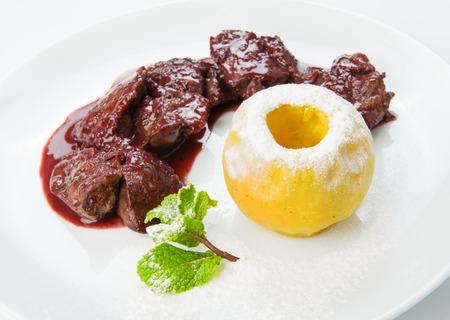Das Essen im Restaurant - Hühnerleber in Granatapfelsauce mit Bratapfel auf dem weißen Hintergrund isoliert
