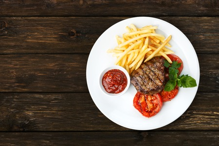 Restaurant food - beef grilled steak isolated at the wooden table, above view