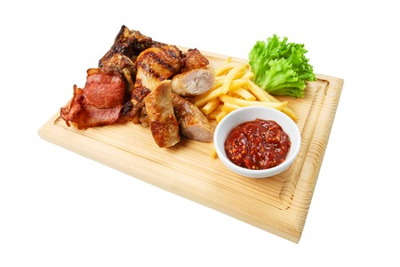 Restaurant food - grilled meat assortment with french fries served on wooden board  isolated at the white background photo