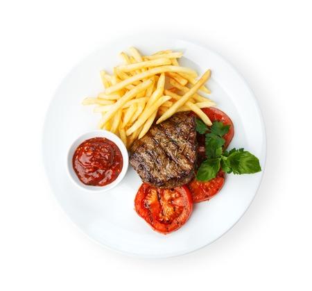 Restaurant eten - rundvlees gegrilde steak die bij de witte achtergrond Stockfoto