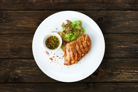 chicken fillet: Restaurant food - chicken fillet grilled steak at wooden table Stock Photo