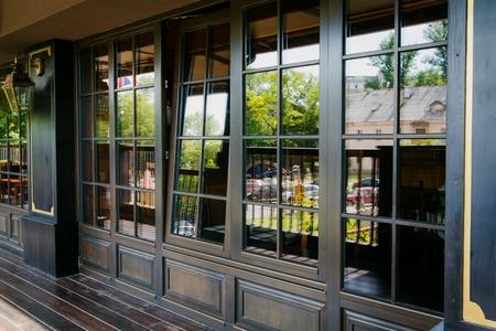 Glasierte Eingang zum luxuriösen Restaurant mit einem geöffneten Fenster
