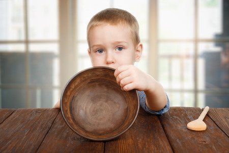 Cute small child boy sitting at wooden table shows empty plate