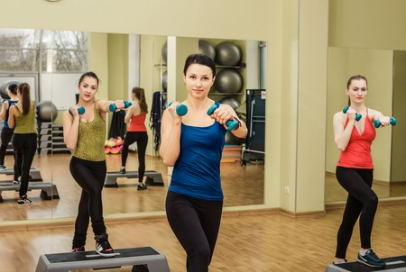 step fitness: Group of women making step aerobics in the fitness class