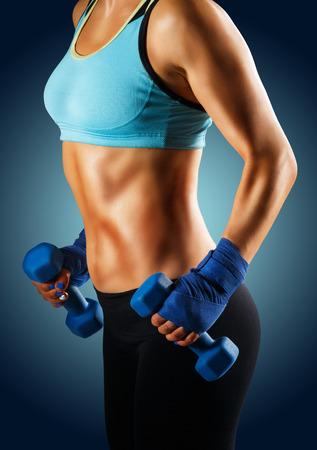 Ideal sportive Torso der jungen Frau mit gebräunte Haut und starke Bauchmuskeln isoliert