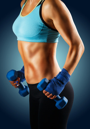 Ideal sportive torso of young woman with bronzed skin and strong abs muscles isolated