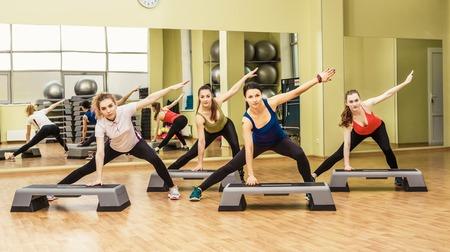 Gruppe von Frauen, die Step-Aerobic im Fitnessklasse